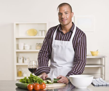 midlife: A young man is in his kitchen and is chopping vegetables to prepare a meal.  He has a glass of wine and is looking at the camera.  Horizontally framed shot.