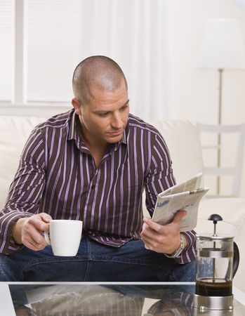 A young, attractive man is sitting at a coffee table, drinking coffee and reading a newspaper.  He is looking away from the camera.  Vertically framed shot. photo