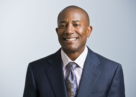 Attractive African American headshot dressed in a suit and tie, facing the camera. Square.