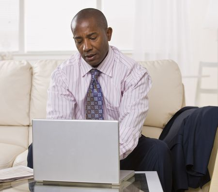 African American male using a laptop on a coffee table. He is looking at the laptop. Square. photo