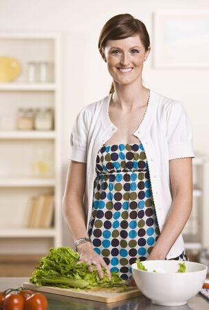 short sleeved: Attractive brunette in kitchen making a salad with a polka dot dress and white cardigan short sleeved sweater. vertical