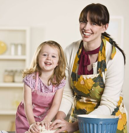 Brunette mom and blond daughter making bread on the kitchen counter, while wearing aprons. Both are kneading dough and looking at the camera. Square photo