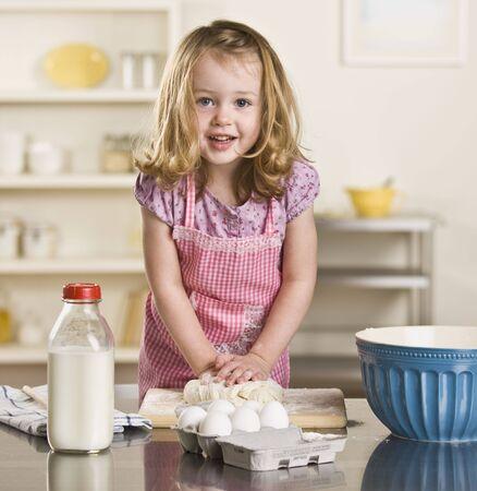 making bread: Cute bambina bionda fare il pane in cucina. Bottiglia di latte, uova e ciotola sul contatore. Piazza