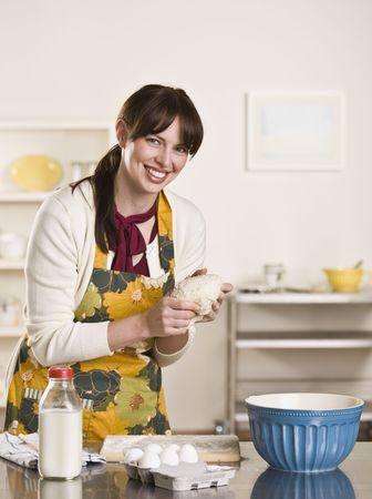Brunette showing bread dough to the camera while smiling and wearing an apron. On the counter is a bowl and milk bottle. photo