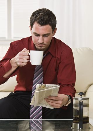 Attractive man drinking coffee while reading the paper sitting on the coach. vertical  photo