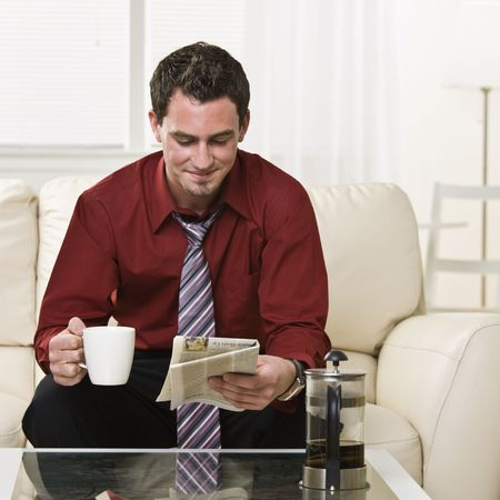 Attractive brunette male drinking coffee and reading the paper while sitting on the coach. square Stock Photo - 5047136