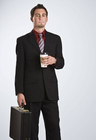 Attractive man with coffee and briefcase facing the camera wearing a business suit and tie. vertical photo