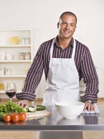 collared shirt: Attractive male chef in the kitchen with vegetables and a glass of wine on the counter. Vertical