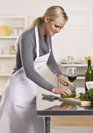 Attractive blond woman slicing cucumber in kitchen while drinking glass of wine looking down.  Vertical photo