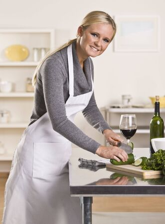 Attractive blond woman slicing cucumber smiling at the camera. Glass of red wine in background. Vertical photo