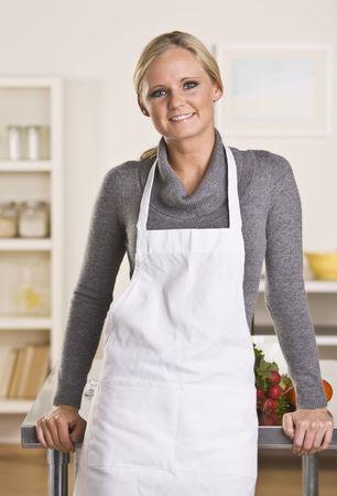 jasschort: Aantrekkelijke jonge blonde met schort in de keuken, leunend op de teller. Stockfoto