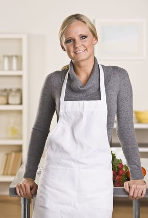aprons: Young attractive blond with apron in the kitchen, leaning on the counter.