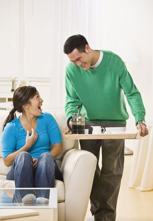 A man standing with coffee service and a woman sitting down with a surprised look on her face. Vertically framed photo. photo