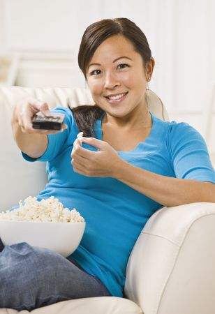 A beautiful young asian woman sitting on a couch. She is holding a bowl of popcorn and is using a remote. She is smiling directly at the camera. Vertically framed shot.