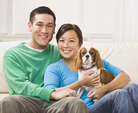 An attractive young asian couple sitting on a couch together and holding a dog.  They are smiling at the camera.  Horizontally framed shot. Stock Photo - 5078335