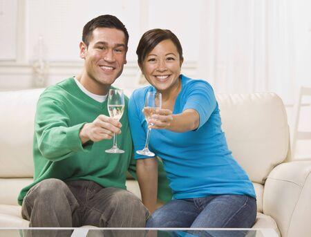 魅力的な若いアジアのカップル シャンパン トーストします。彼らが装着されているソファの上に一緒にし、カメラに笑顔します。水平方向にフレームのショット。