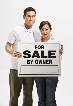 A worried looking asian couple holding a For Sale sign.  They are looking directly at the camera. Vertically framed shot.