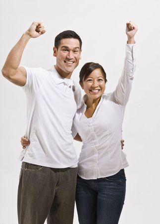 An attractive young asian couple cheering with their fists in the air.  They are smiling at the camera.  Vertically framed shot. Stock Photo