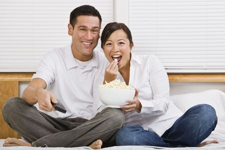 Attractive asian couple sitting on a bed together and eating popcorn. Horizontally framed shot.