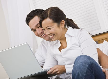 couple on couch: Attractive asian couple smiling while looking at a laptop screen together. Horizontally framed photo.