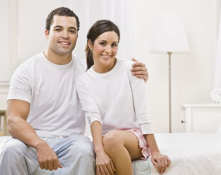 Attractive couple hugging and sitting together in their bedroom. Horizontally framed photo. photo