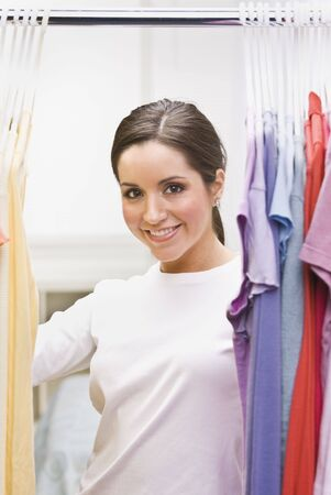 A beautiful brunette looking through clothing in a closet.  She is smiling at the camera. Vertically framed shot.