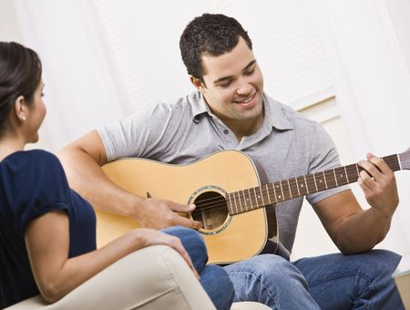 they are watching: A young and attractive couple sitting on a couch with a guitar.  The male is playing the guitar and the female is watching.  They are smiling.  Horizontally framed shot.