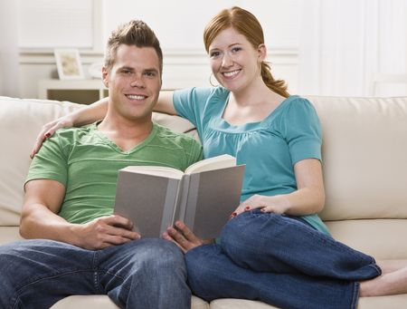 幸いにも、ソファで一緒に読んで、魅力的な若いカップル。彼らはカメラで直接笑っています。水平方向にフレームのショット。