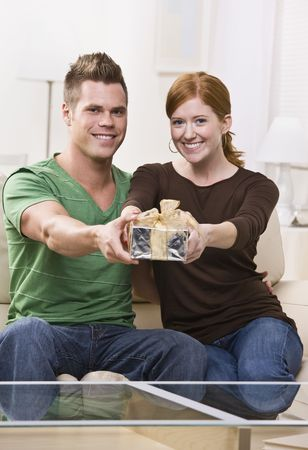 An attractive and young caucasian holding out a present and smiling.  They are seated on a couch in a living room and are looking directly at the camera. Vertically framed shot. photo