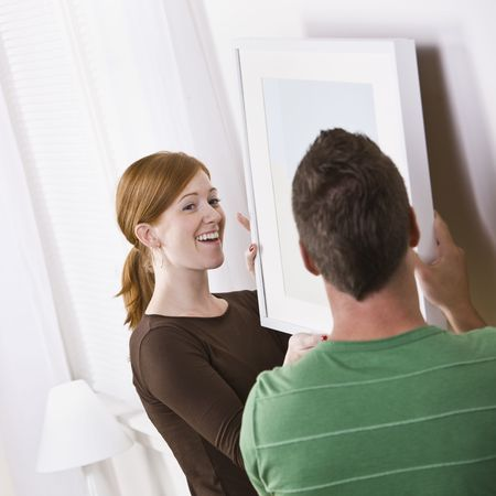 An attractive young couple hanging a picture frame in their home. Square composition. Stock Photo - 5078308