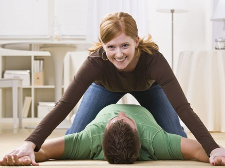 A playful young woman pinning a man to the floor. She is smiling directly at the camera.  Horizontally framed shot. photo