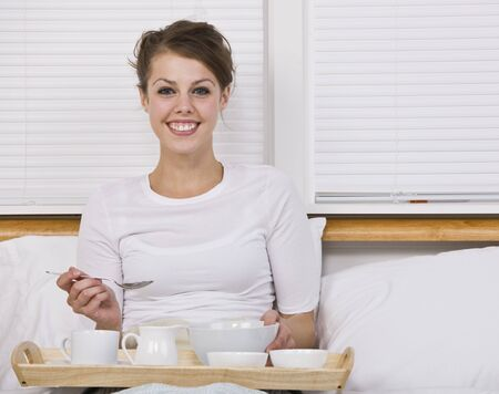 An attractive young woman eating breakfast in bed. She is smiling at the camera. Horizontally framed shot. Stock Photo - 5078243