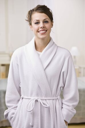 An attractive young woman wearing a bathrobe and smiling at the camera.  Vertically framed shot. Stock Photo - 5078188