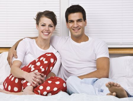 An attractive couple smiling and sitting in bed together.  Horizontally framed shot. Stock Photo - 5078298