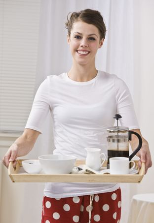 Attractive woman serving coffee in a french press. She is smiling and looking at the camera. Vertically Framed Photo. Stock Photo - 5078290