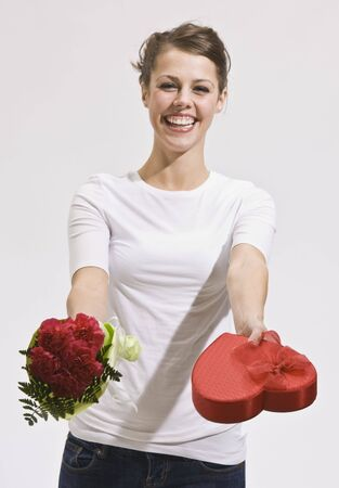 Smiling caucasian woman holding out Valentine's Day roses and candy while looking at the camera. Vertically framed photo. Stock Photo - 5078288