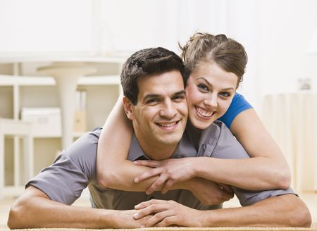 An attractive young couple posing together. The female is on his back and has her arms around his neck affectionately. They are smiling at the camera. Horizontally framed shot.