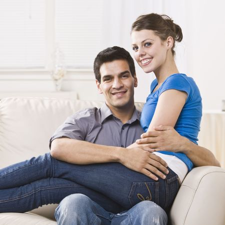An attractive young couple relaxing together in their home.  The woman is sitting on the mans lap and they are smiling at the camera happily. Square composition. photo