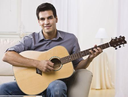down sitting: An attractive and relaxed looking man sitting on a couch and playing the guitar.  He is smiling at the camera. Horizontally framed shot.