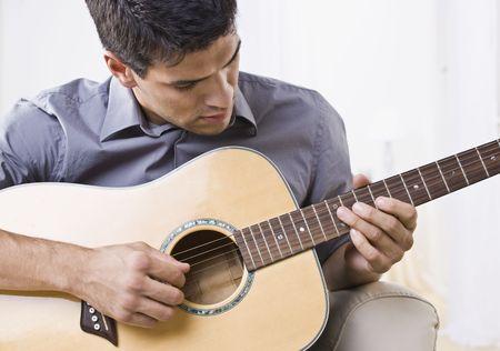 guitarra acustica: Un atractivo hombre tocando una guitarra ac�stica. Horizontalmente enmarcada disparo. Foto de archivo