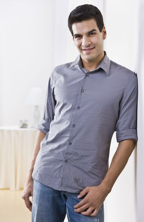 midlife: An attractive man posing.  He is smiling and is leaning against the wall while looking at the camera. Vertically framed shot.