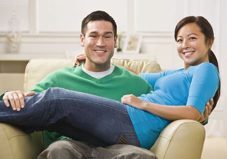 Attractive Asian Couple relaxing together on their living room couch. Horizontally framed photo. photo