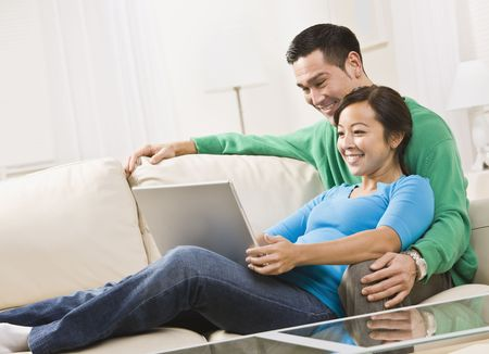 An attractive young couple on a couch, viewing a laptop screen. They are smiling. Horizontally framed shot. Stock Photo - 5120653