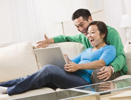 매력적인 젊은 부부 함께 소파에 앉아 및 노트북 화면보기. 그들은 웃고있다. 가로 프레임 된 샷입니다.