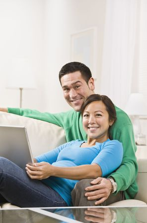An attractive young couple sitting on a couch together and holding a laptop.  They are smiling at the camera. Vertically framed shot. Stock Photo - 5120685