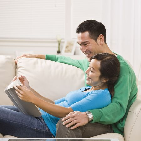 A young couple is seated together on their living room couch.  They are reading a book together, smiling, and looking away from the camera.  Square framed shot. photo