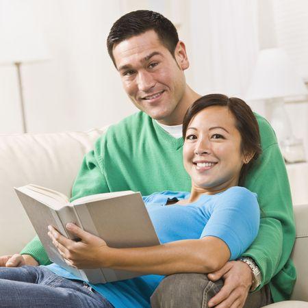 本と一緒にソファに座って、魅力的な若いカップル。 女性は男性の膝の上に座っています。 彼らはカメラで直接笑っています。正方形のフレームのショット。