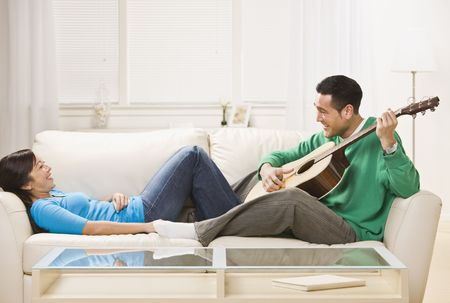 wooing: Asian couple on couch playing guitar. Man serenading the woman. Horizontal
