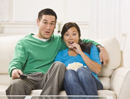 A shocked or surprised looking young couple watching television together.  They are seated on a couch and have a bowl of popcorn. The man is holding a remote control and they are looking directly at the camera. Horizontally framed shot. Stock Photo - 5120718