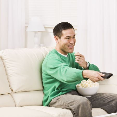 couch: A man seated on a couch and using a remote control for T.V. He is eating popcorn and smiling. Square framed photo. Stock Photo